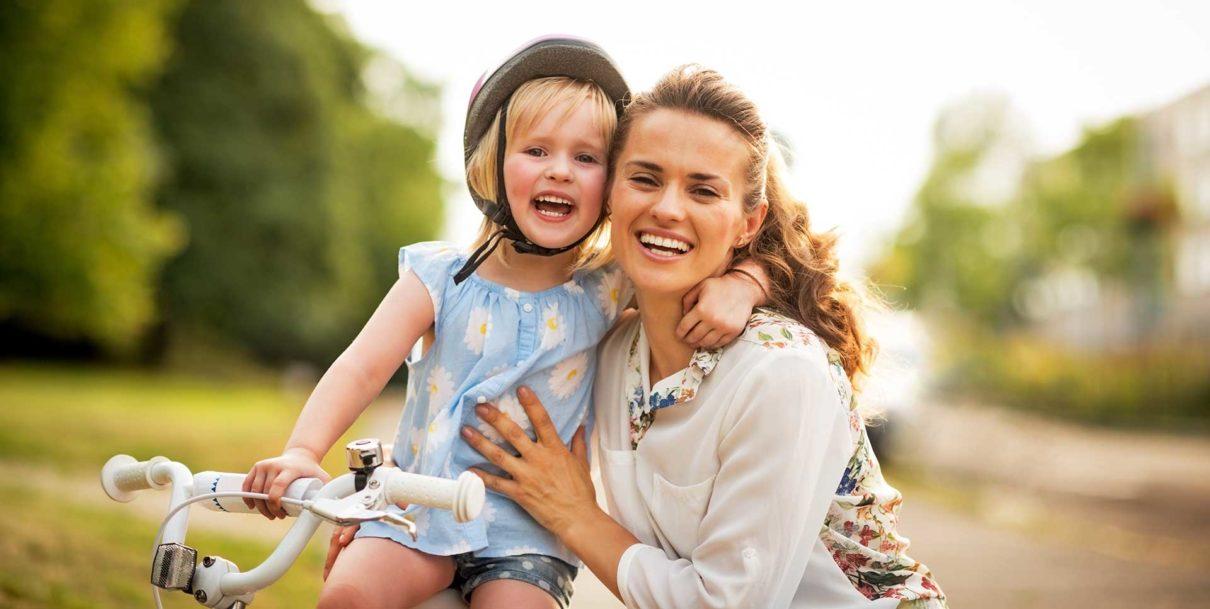 Mom and girl smiling on bike