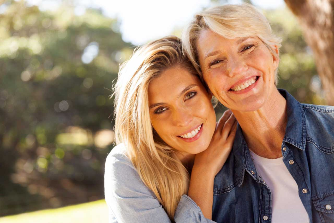 Two women smiling with a tooth denture